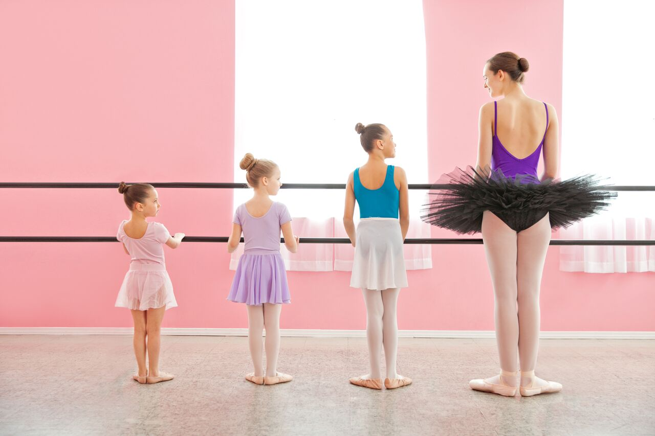 recital dancers of all ages facing ballet barres