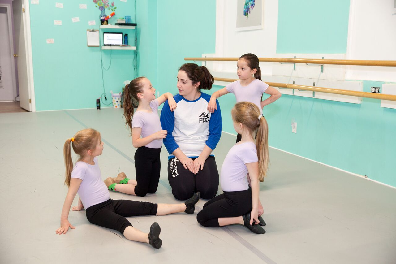 Mini Dancers take a break with Miss Lainy to relax after a hot hip-hop class.